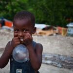 En dreng leger med et kondom i en af de store teltlejre i Petionville, Port au Prince